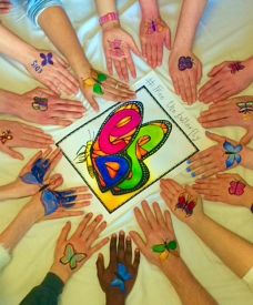 Hands with butterflies drawn on them surrounding the EDIS butterfly logo